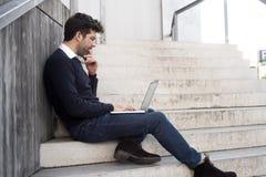 Junger Mann mit Computer und Zweifeln Stockbild