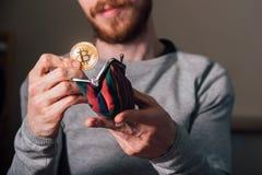 Junger Mann mit dem Bart, der bitcoin in Geldbörse setzt stockfotos