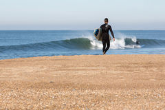 Junger Mann mit dem Brandungsbrett, das auf den Strand geht Stockbild