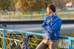 Junger Mann mit dem Fahrrad, das auf Park-Brücken-Geländer sich lehnt Stockbild