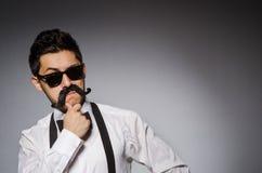 Junger Mann mit dem falschen Schnurrbart lokalisiert auf Grau Stockfoto