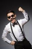 Junger Mann mit dem falschen Schnurrbart lokalisiert auf Grau Stockbild