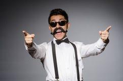 Junger Mann mit dem falschen Schnurrbart lokalisiert auf Grau Stockbilder