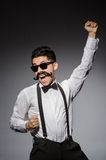 Junger Mann mit dem falschen Schnurrbart lokalisiert auf Grau Stockfotografie