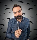 Junger Mann mit dem geformten Schnurrbart des Passfotoautomaten Lizenzfreies Stockfoto
