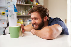 Junger Mann mit dem Handy, der zu Hause auf Kaffeetasse stillsteht Lizenzfreies Stockbild