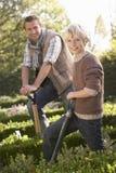 Junger Mann mit dem Kind, das im Garten arbeitet Lizenzfreie Stockfotos