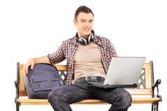 Junger Mann mit dem Laptop, der auf einer Holzbank sitzt Lizenzfreies Stockfoto