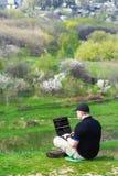 Junger Mann mit dem Laptop, der draußen arbeitet Stockfotos