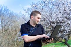 Junger Mann mit dem Laptop, der draußen arbeitet Lizenzfreies Stockfoto