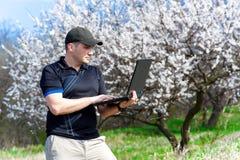 Junger Mann mit dem Laptop, der draußen arbeitet Lizenzfreie Stockfotografie