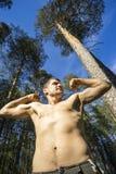 Junger Mann mit dem nackten Torso vor dem hintergrund der Kiefer im Wald Stockbild
