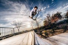 Junger Mann mit dem Roller, der einen Sprung auf Skatepark während des Sonnenuntergangs macht stockbilder