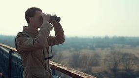 Junger Mann mit dem roten Haar herein im kakifarbigen Mantel, der durch Ferngläser von der Brücke schaut stock video footage