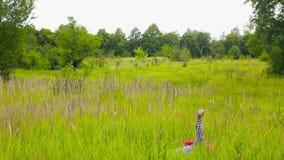 Junger Mann mit dem roten Umhang, der durch das Feld, abfallend läuft stock video