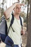 Junger Mann mit dem Rucksack, der Augen im Wald abschirmt Lizenzfreies Stockbild