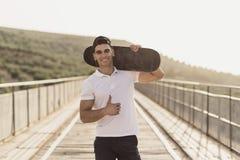 Junger Mann mit dem Skateboard glücklich auf einer Brücke lizenzfreie stockfotos