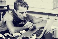 Junger Mann mit dem Thermometerkranken, der seine Nase in seinem Wohnzimmerarbeitsnotizbuch Schwarzweiss durchbrennt Lizenzfreies Stockbild