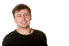 Junger Mann mit dem unsicheren verwirrten Ausdruck, lokalisiert auf Weiß Stockfotografie