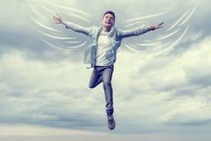 Junger Mann mit den gezogenen Flügeln, die in Himmel fliegen Stockbild