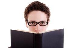 Junger Mann mit den Gläsern, blickend über einem geöffneten Buch Lizenzfreie Stockfotos