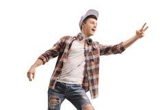 Junger Mann mit den Kopfh?rern, die ein Friedenszeichen machen stockfoto