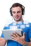 Junger Mann mit den Kopfhörern, die an einem Tablette-PC arbeiten Stockfotografie