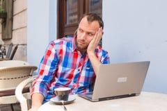 Junger Mann mit den Kopfschmerzen, die im Café mit Laptop und Kaffee sitzen. Lizenzfreie Stockbilder