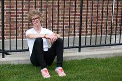 Junger Mann mit den nerdy Gläsern, die durch Zaun sitzen Lizenzfreie Stockfotografie