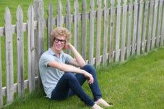 Junger Mann mit den nerdy Gläsern, die durch Zaun sitzen Stockfoto