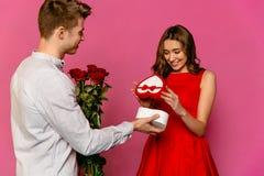 Junger Mann mit den roten Rosen, die ein Geschenk für seine Freundin machen Stockbilder