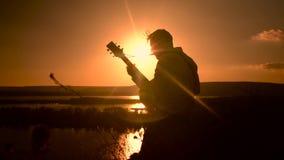 Junger Mann mit der Akustikgitarre, die auf die Oberseite eines Hügel- und Anfangsspielens klettert stock footage