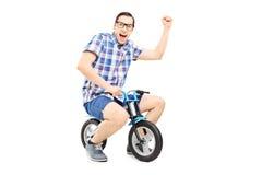 Junger Mann mit der angehobenen Faust, die ein kleines Fahrrad reitet Lizenzfreies Stockfoto
