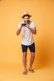 Junger Mann mit der Retro- Kamera, die Foto macht Lizenzfreie Stockbilder