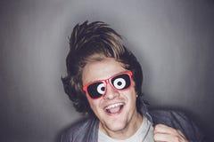 Junger Mann mit der Sonnenbrille, die seinen Kopf rüttelt Lizenzfreies Stockbild