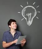Junger Mann mit der Tablette, die nach einigen Ideen sucht Lizenzfreies Stockbild
