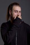 Junger Mann mit einem Bart bedeckt ihren Mund Lizenzfreie Stockfotos