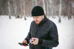 Junger Mann mit einem Bart draußen im Schnee im Winter Lizenzfreie Stockfotografie