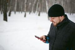 Junger Mann mit einem Bart draußen im Schnee im Winter Stockbild