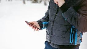 Junger Mann mit einem Bart draußen im Schnee im Winter Stockfoto