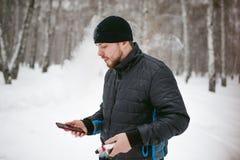 Junger Mann mit einem Bart draußen im Schnee im Winter Stockbilder