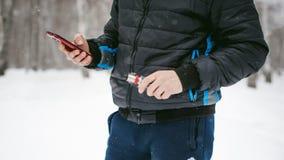 Junger Mann mit einem Bart draußen im Schnee im Winter Stockfotografie