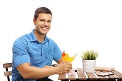 Junger Mann mit einem Cocktail, das an einem Tisch sitzt Stockbilder