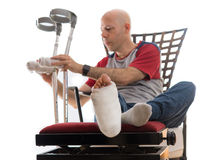 Junger Mann mit einem gebrochenen Knöchel und einer Beinform stockbilder