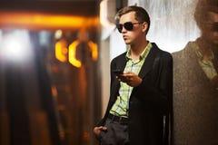 Junger Mann mit einem Handy an der Wand Lizenzfreie Stockfotografie