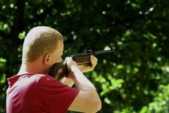 Junger Mann mit einem Jagdgewehr Lizenzfreie Stockfotos