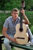 Junger Mann mit einem quitar durch den Fluss Stockfoto
