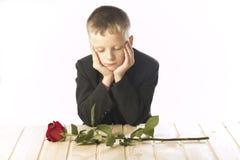 Junger Mann mit einem Roten stieg Der Mann sitzt am Tisch Lizenzfreies Stockbild