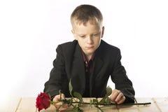 Junger Mann mit einem Roten stieg Der Mann sitzt am Tisch Stockfoto