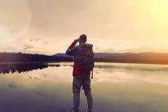 Junger Mann mit einem Rucksack, der nahen See steht und durch Ferngläser schaut Lizenzfreie Stockbilder